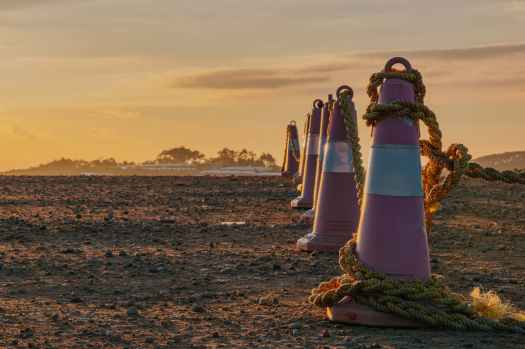 photo of traffic cones with ropes during dawn